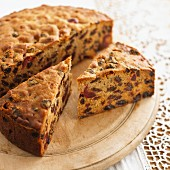 Fruitcake, partly sliced, on a wooden board