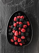 Fresh blackberries and raspberries in a dish (view from above)