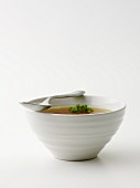 Clear broth with parsley in a soup bowl