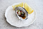 A fresh oyster with Thai chilli dressing and lemon wedges on rock salt