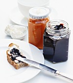 Bread topped with cream cheese and plum jam, with quince jelly in a jam jar