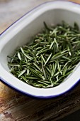 Fresh rosemary leaves in an enamel bowl