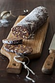 Chocolate Biscuit Salami with Walnuts and Rum (no bake) on cutting board