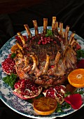 Crown roast of pork on a black background with fruits
