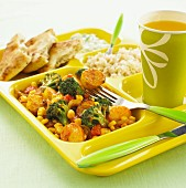 Vegetable curry with rice and a drink on a canteen tray