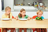 Three children at a table in the kitchen, staring at a plate full of vegetables