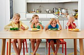 Four children sit, bored, in front of plates of vegetables