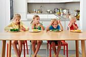 Vier Kinder sitzen gelangweilt vor Tellern mit Gemüse