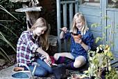 Two girl potting flower pots