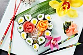 Assorted sushi in the shape of a heart with orchids and chopsticks