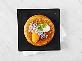 Blini topped with caviar, onion and sour cream