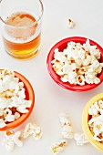 Popped Corn in Colorful Bowls with Glass of Beer. From Overhead