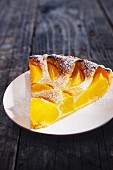 A slice of peach tart with icing sugar