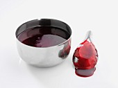 Berry sauce in a metal bowl and on a spoon
