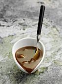 Liquorice sauce in a bowl with a spoon