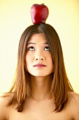 Woman balancing apple on head