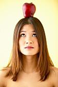 Frau balanciert Apfel auf dem Kopf