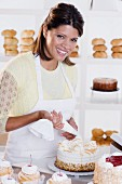 Portrait of woman decorating cake at bakery