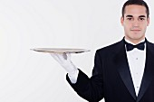Portrait of male waiter balancing tray