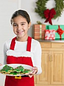 Young girl in a Santa apron holding a plate of Christmas cookies