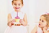 Zwei Mädchen mit Cupcake zum Geburtstag