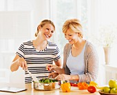 A mother and her adult daughter cooking together in the kitchen