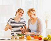 Mutter & erwachsene Tochter beim gemeinsamen Kochen in der Küche