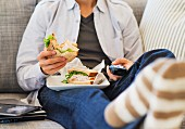 A young man sitting on the sofa holding a sandwich and a remote control