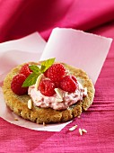 Pancake topped with raspberry cream and slivered almonds