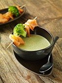 Cream of broccoli soup with a smoked salmon skewer