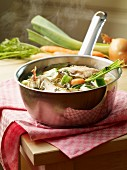 Chicken stock with vegetables in a saucepan