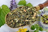 A mix for herbal tea, made with lemon balm, passion flowers, St. John's wort, hops, lavender and orange flowers on a brass scoop