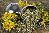Dried goldenrod tea leaves in a tea ball, and fresh flowers