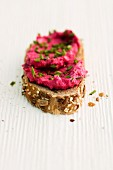 A slice of bread with beetroot cream cheese