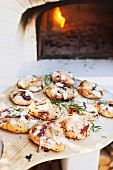 Mini pizzas with tomatoes and rosemary on a pizza paddle in front of a wood-fired oven