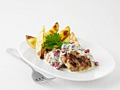 Burgers with cranberries in a cream sauce with potato wedges (Sweden)