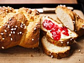 Plaited bread with butter and jam