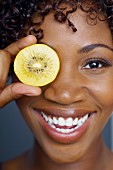 African woman holding fruit slice in front of eye