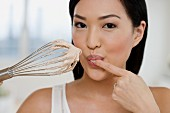 Close up of Asian woman tasting batter on whisk