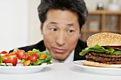 Asian man looking at salad and hamburger