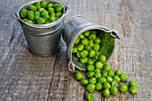 Peas in a bucket of brass on wooden background