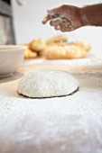 A baker scattering flour over bread dough