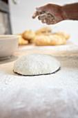 Bäcker bestreut Brotteig mit Mehl