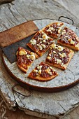 Bacon Jam on grilled flatbread with melted gorgonzola cheese on rustic wooden surface