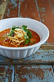 Thai Khao Soi Noodle Soup. made with egg noodles, coconut milk, yellow curry, cilantro, red and green onion, and crispy fried noodles.