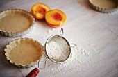 Work surface for tart making, including tart pans with pastry, fresh peaches and flour