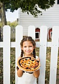Hispanic girl holding homemade pie