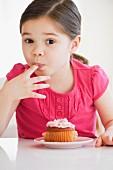 Mädchen mit Cupcake schleckt sich Zuckerguss von den Fingern