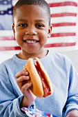 African American boy eating hot dog in front of American flag