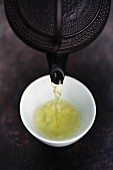 Close up of Japanese green tea being poured from teapot into cup